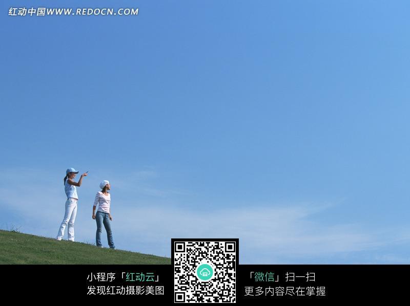 蓝天白云下站在 草地 上眺望的两个 美女 图片