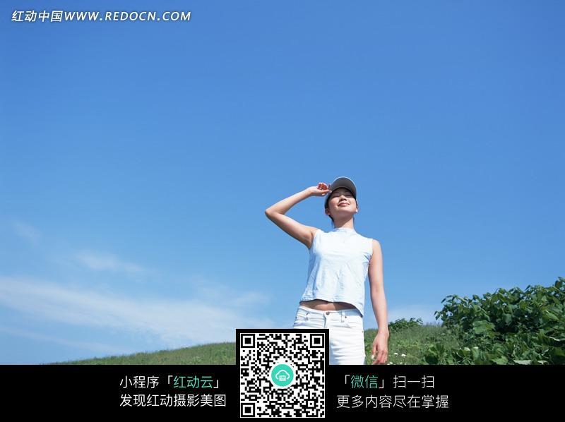 蓝天白云下单手抚帽站在 草地 上 美女 图片