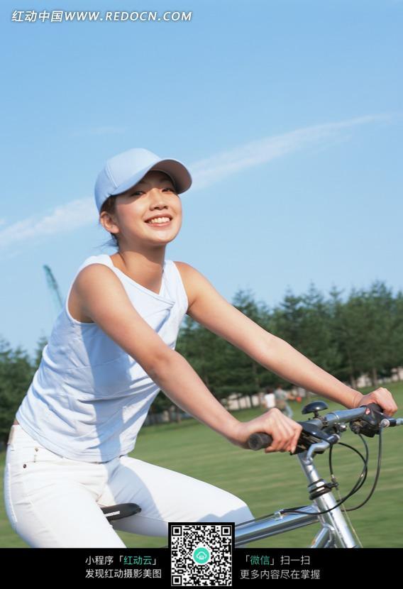蓝天下骑自行车的美女图片