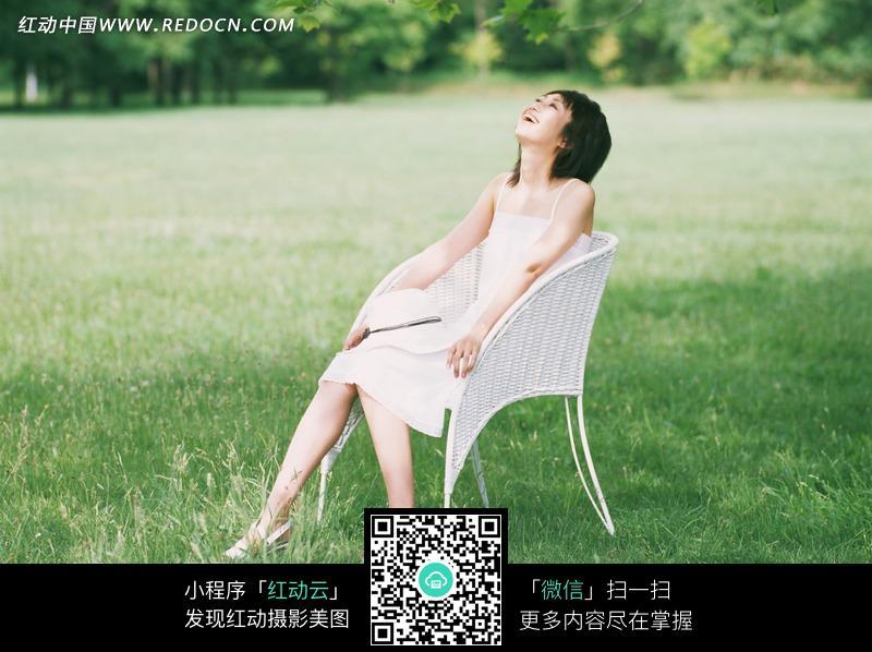 坐在草地椅子上仰头大笑的美女图片 日常生活