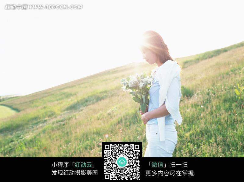 阳光下捧着一束野花走在草地上的美女图片