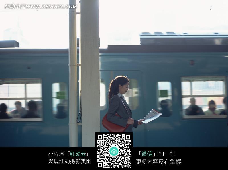 美女 轻轨-轻轨站台旁看报纸的职业装美女