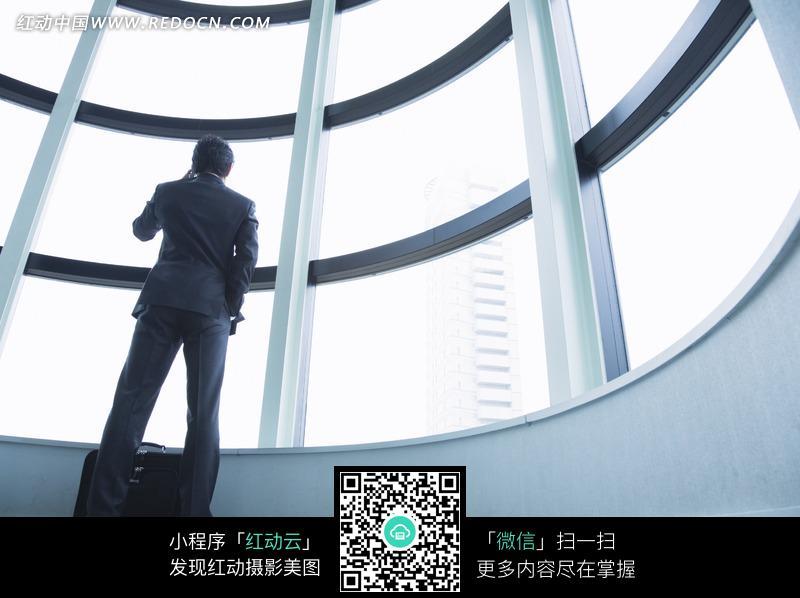 右手插兜站在窗边打电话的男人图片