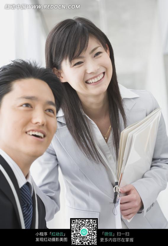 微笑的男人和抱着文件的女人图片