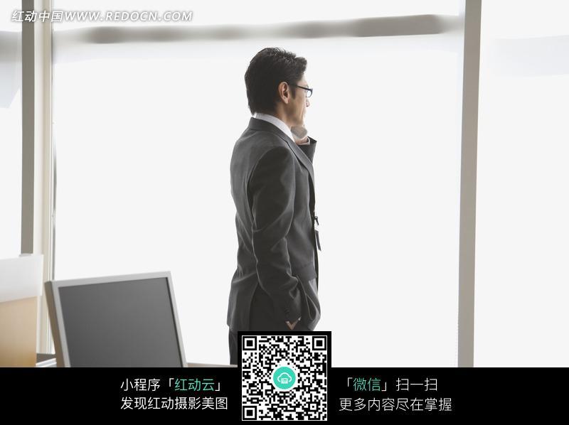 办公室站在窗边的男人打电话图片