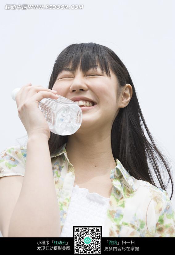 手拿矿泉水眯眼微笑的长发女子