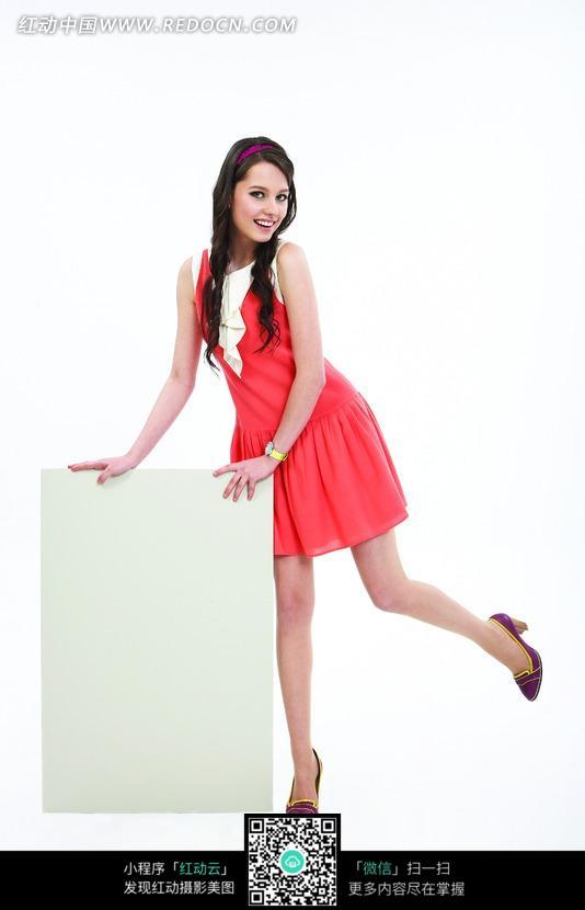 手扶木板单脚站立的红裙美女图片