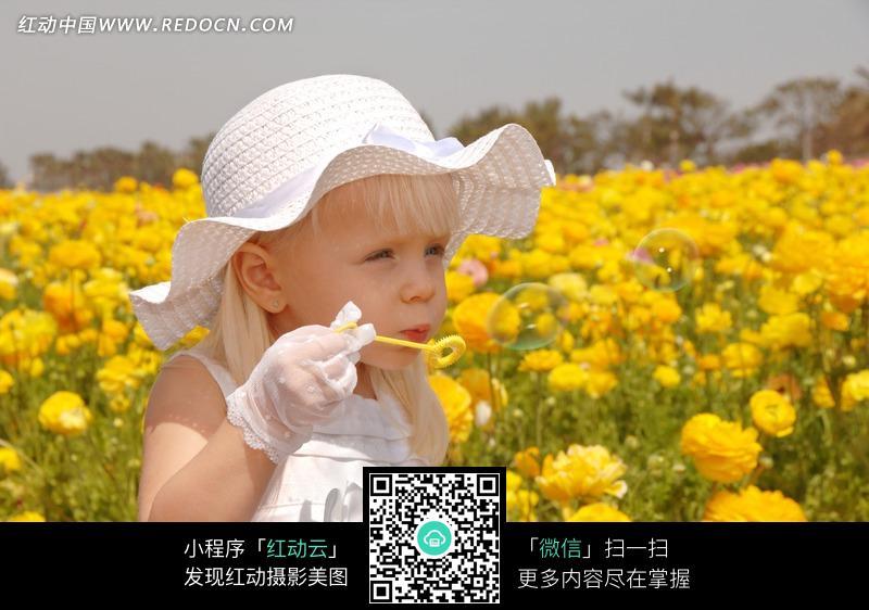 花丛中吹泡泡的小女孩图片