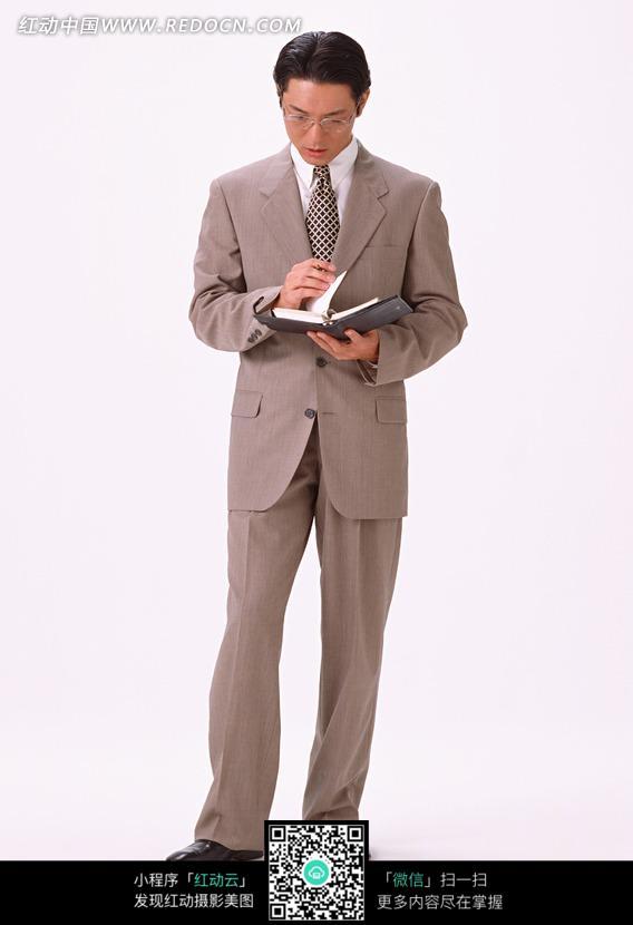 站着低头看记事本的职业装男士图片
