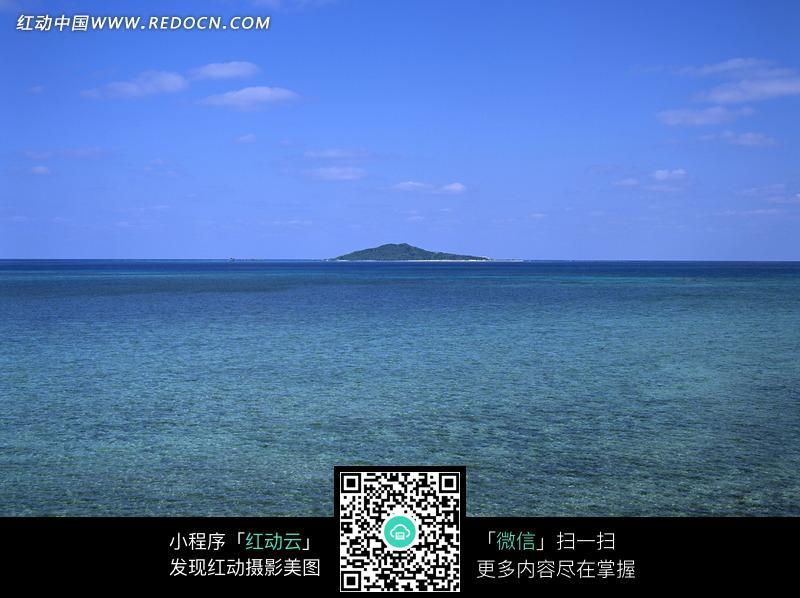 蓝天白云下清澈海水中的绿色小岛图片