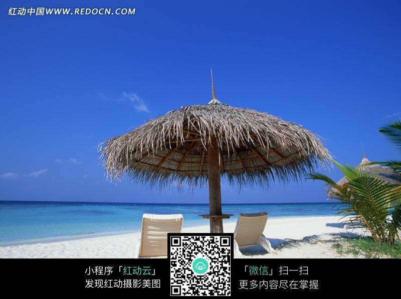 白色沙滩上草编的遮阳伞和两个躺椅