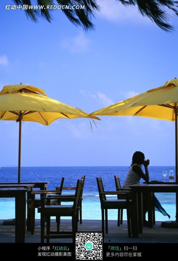 海边沙滩上太阳伞下桌旁看海的美女图片