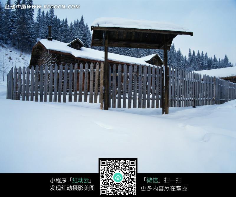 雪地中围着木栅栏的小木屋