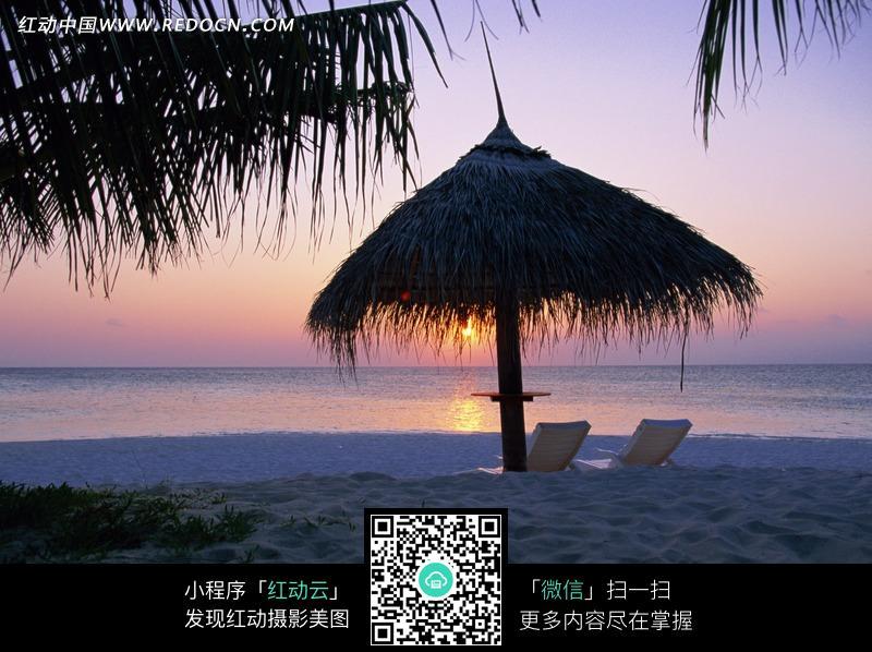 海边沙滩上的茅草亭和椅子图片