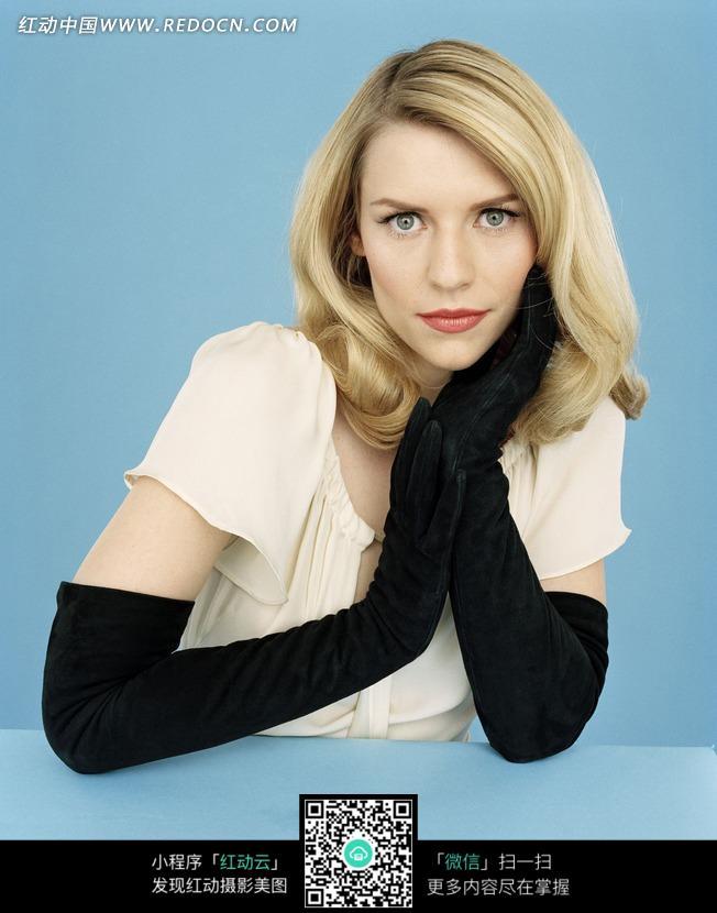 戴着黑手套单手托腮的外国美女图片