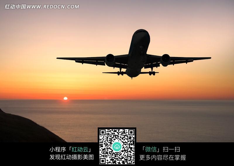夕阳下飞翔飞机图片
