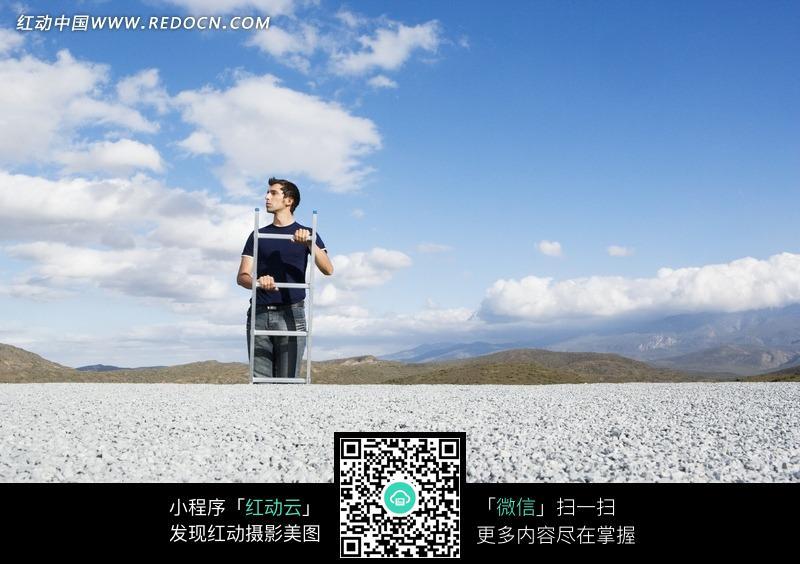免费素材 图片素材 人物图片 职业人物 在石子地上正在爬梯子的男人