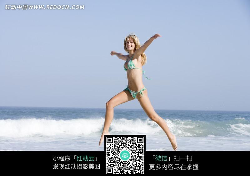 穿着绿点比基尼在沙滩上跳舞的美女图片