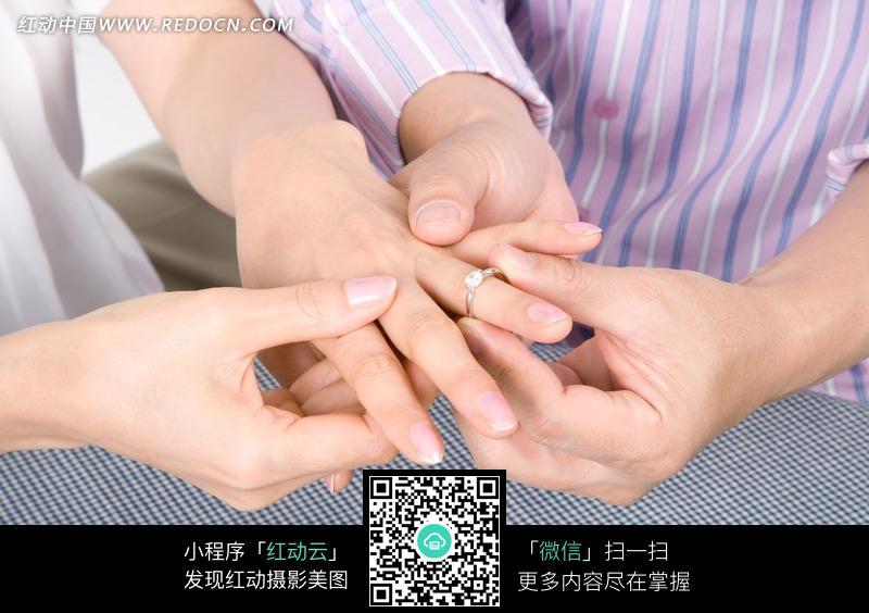 男人为女人带上戒指的手部特写图片