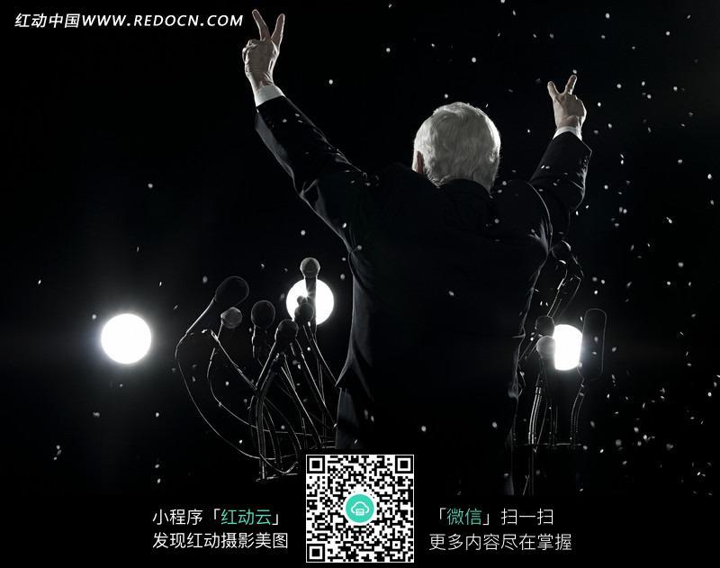 演讲台上举手庆祝的政治人物的背影图片