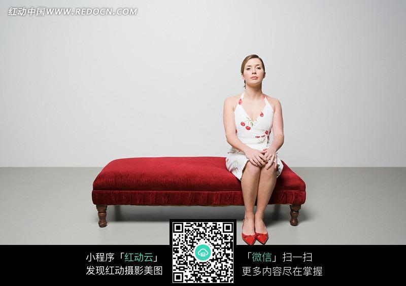 端坐在红色沙发上的白裙美女图片