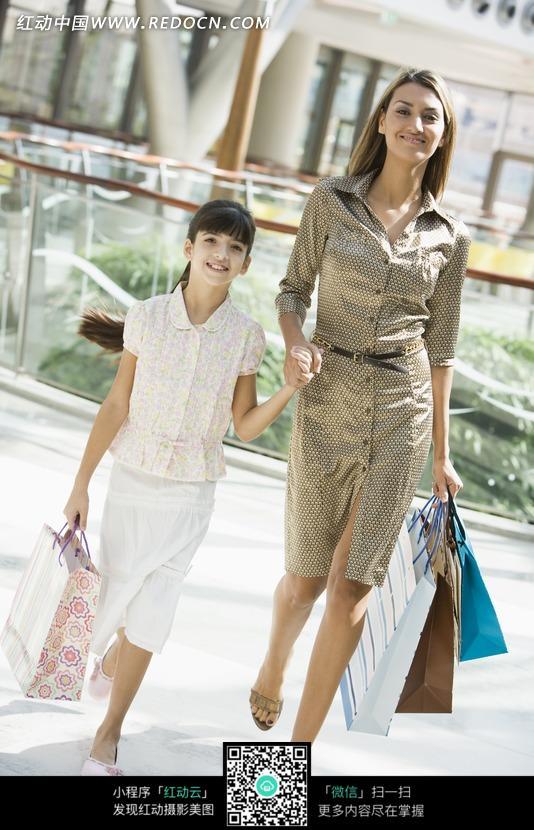 提着购物袋手牵手的一对母女