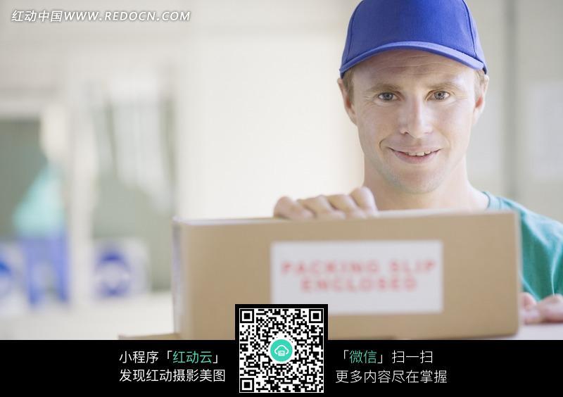 纸箱后戴着帽子微笑的外国人图片