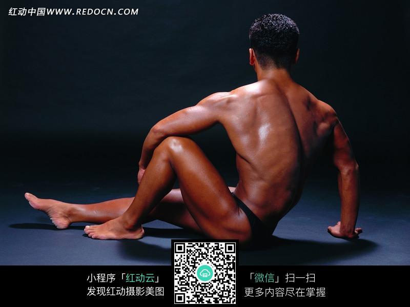 坐着展示背部肌肉的健美先生