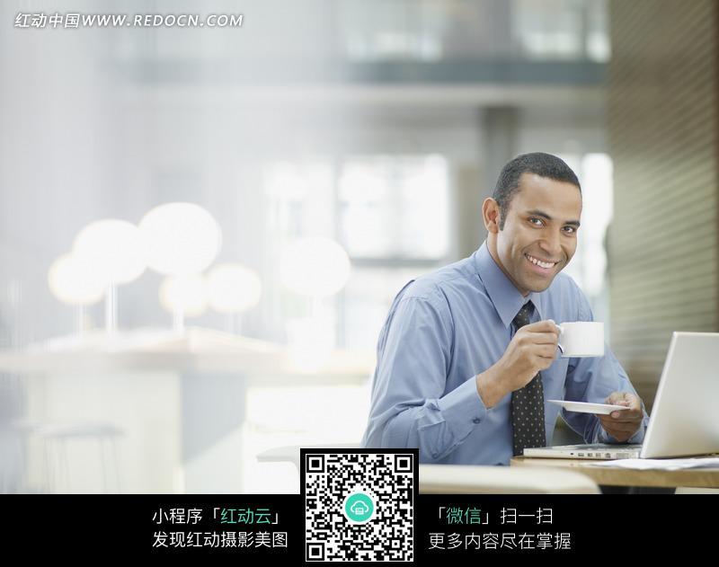 > 人物图片 > 职业人物 > 坐在笔记本电脑前端着杯子的外国商务男士