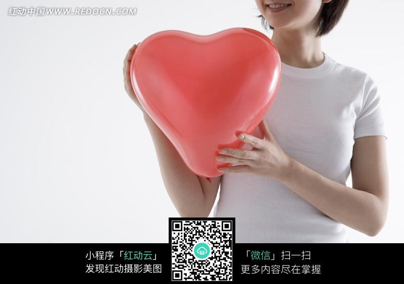 手机 心形 红色 胸口/把红色心形气球放在右胸口的手