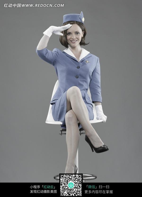 跷腿坐着敬礼的外国空姐图片