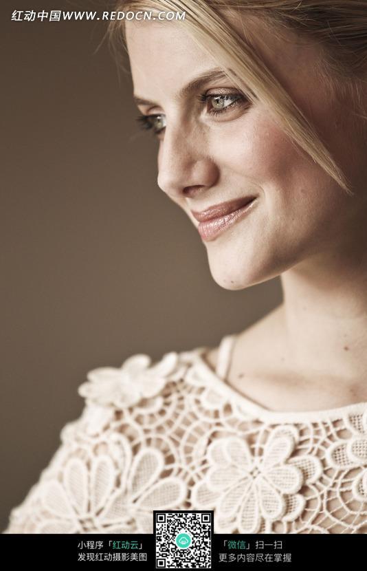 低头侧脸微笑的外国美女图片