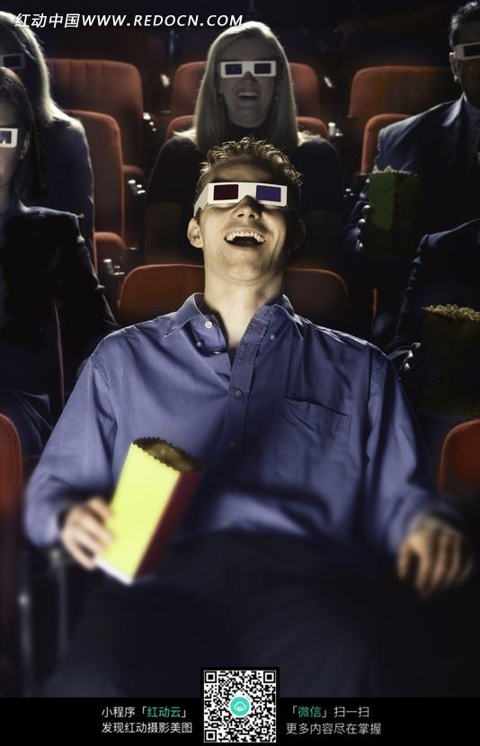 在电影院带着3d眼镜大笑着看电影的人