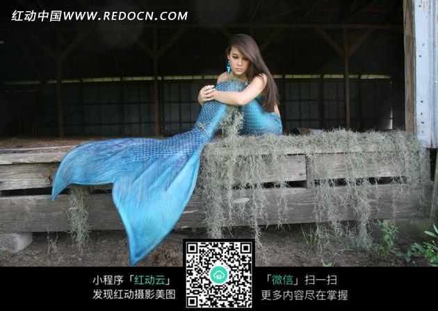 拖着蓝色尾巴的扮成人鱼小姐的美女图片