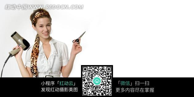 右手拿吹风机左手拿剪刀的理发师美女图片