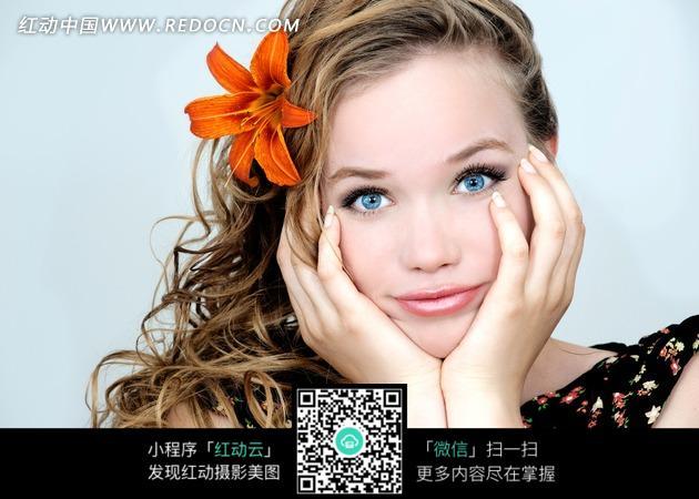 双手托着脸部蓝色眼睛皮肤光滑的外国美女