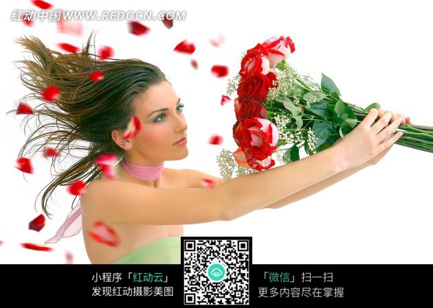 双手捧红色玫瑰花的美女侧面