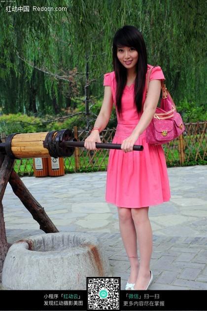 古井旁穿着粉色连衣裙的美女图片