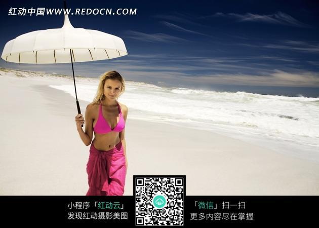 沙滩上打伞的外国美女图片