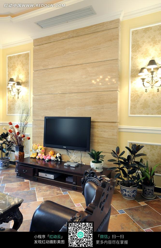 客厅里电视柜边上的鲜花和绿色植物