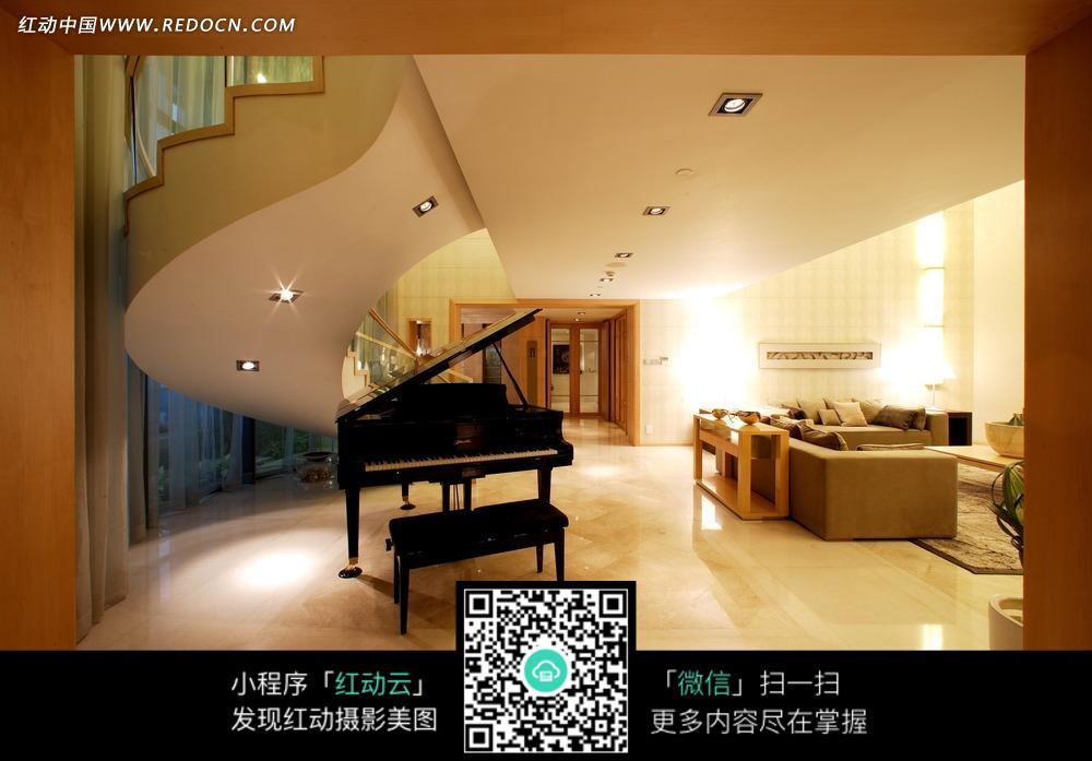 旋转楼梯下的黑色钢琴和客厅沙发椅图片