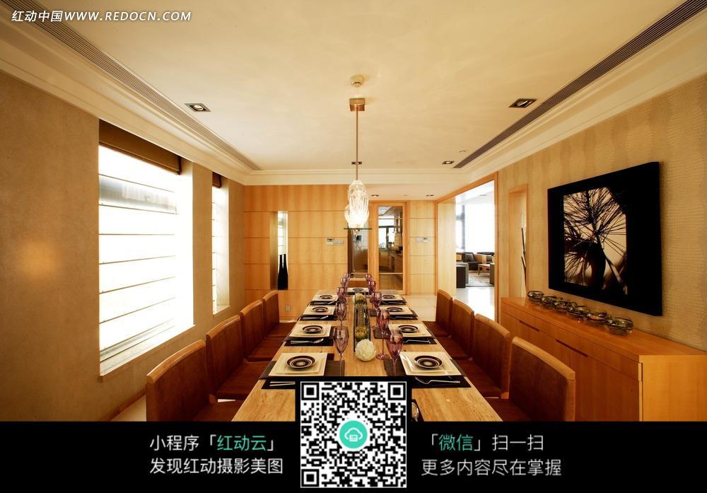餐厅内的长形餐桌椅和墙壁上的黑色装饰画