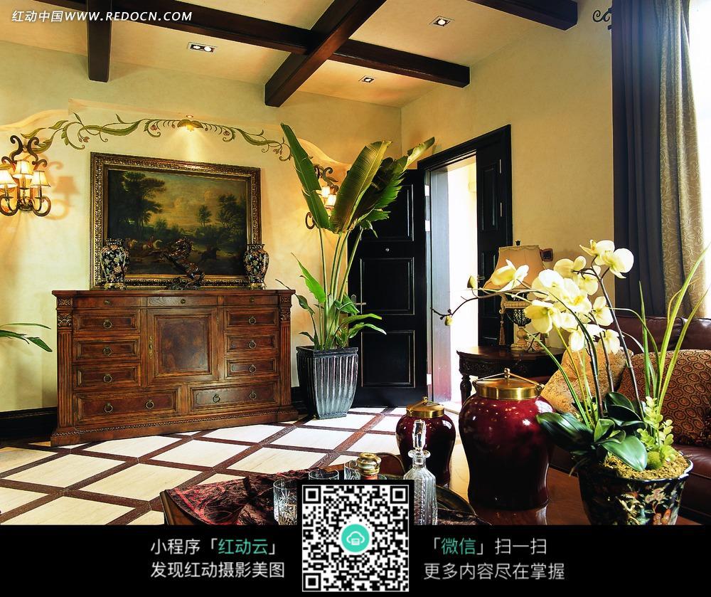 墙壁上的装饰画实木柜子和绿色室内植物