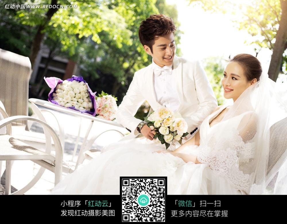 拿着白色玫瑰花的婚纱美女和白西装男士图片