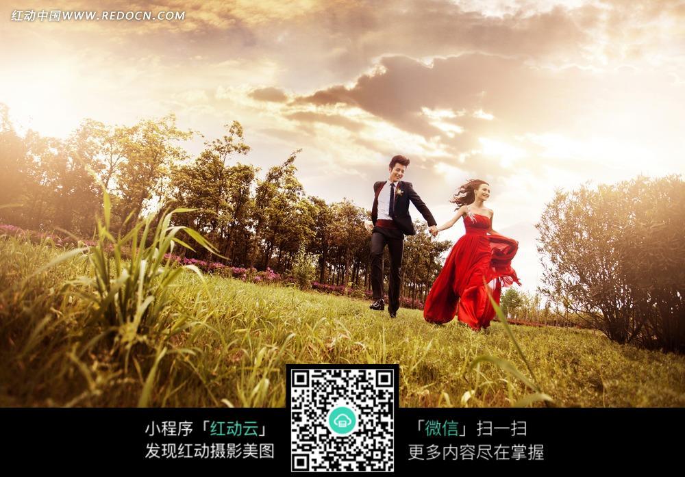 草地上男士牵着红衣美女的手奔跑