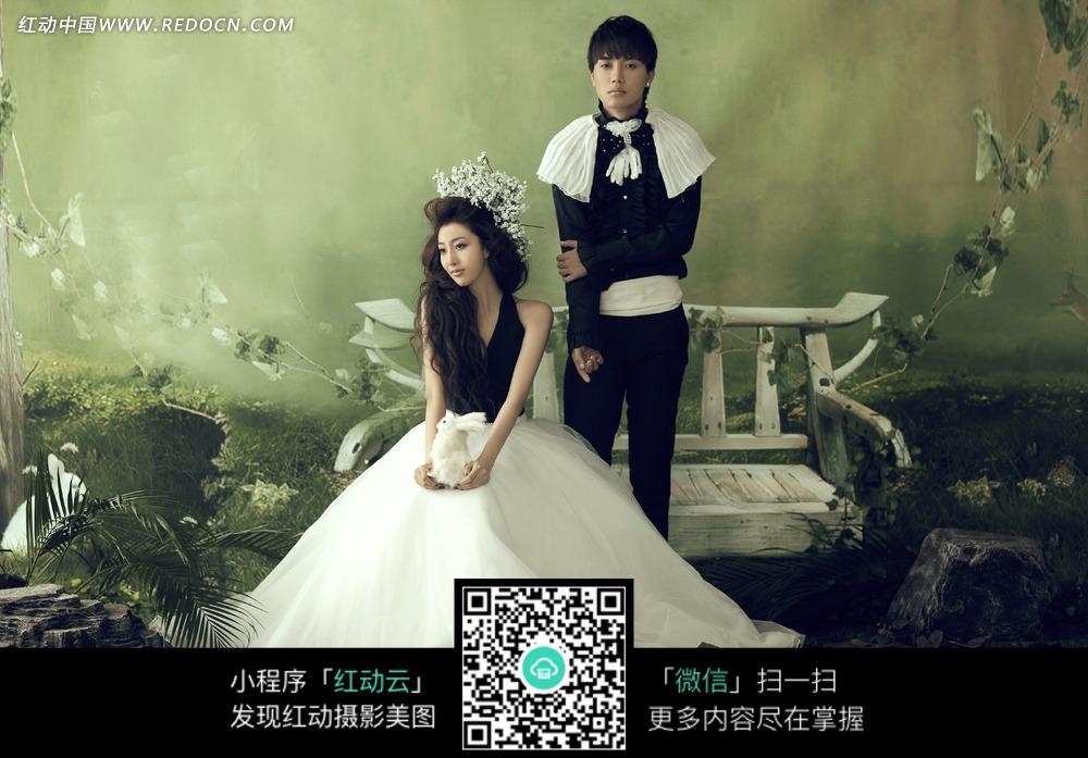 绿色墙壁前的黑衣男士和坐在椅子上的婚纱美女