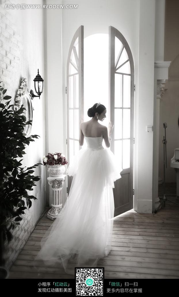 拱门前穿着白色婚纱的美女背影