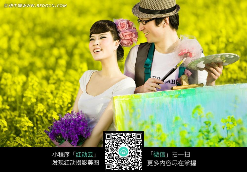 花丛中帅哥拿画板做画美女手捧鲜花的一对情侣图片