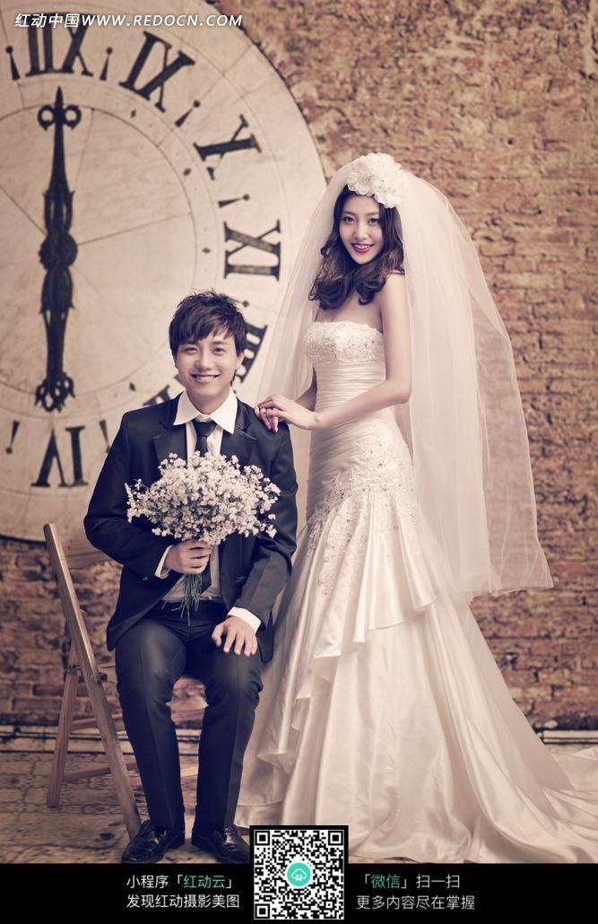 墙壁上的钟表和婚纱美女及拿着白花的男士