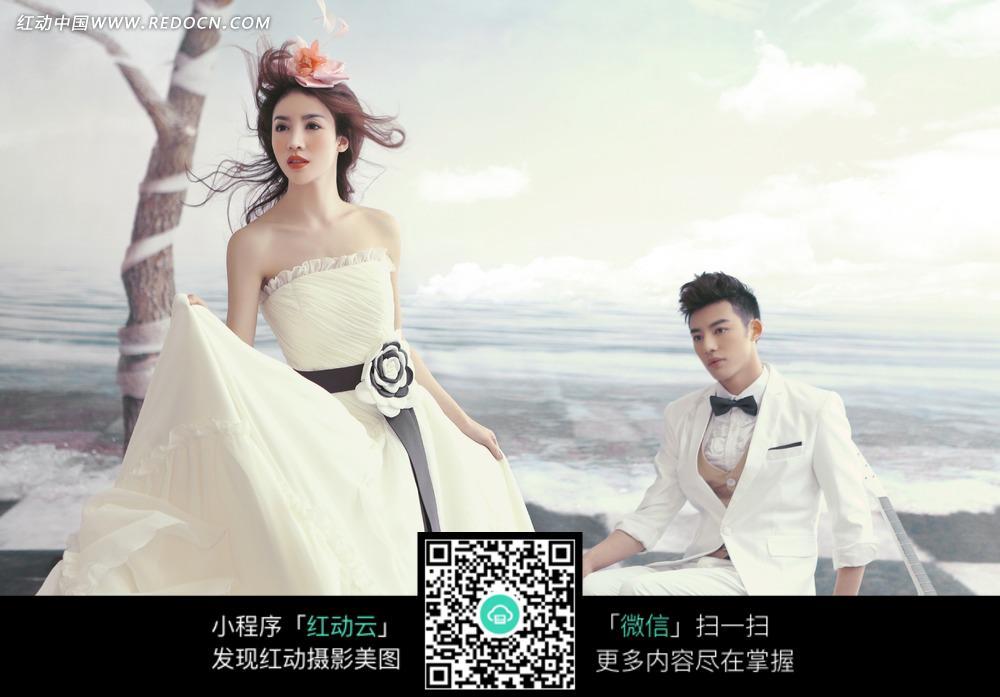 大海边系着黑色腰带的婚纱美女和白衣男士图片